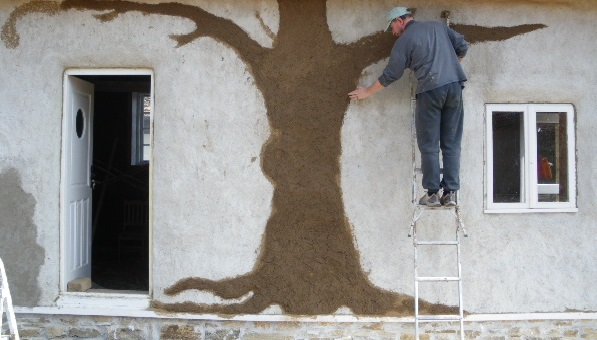 Applying cob to the exterior of our strawbale studio